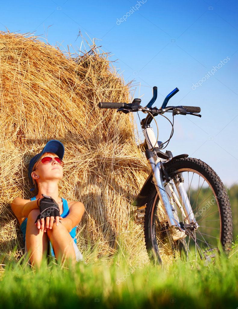 Young woman with bicycle sitting near straw heap and looking to a sky  Stock Photo #8149485