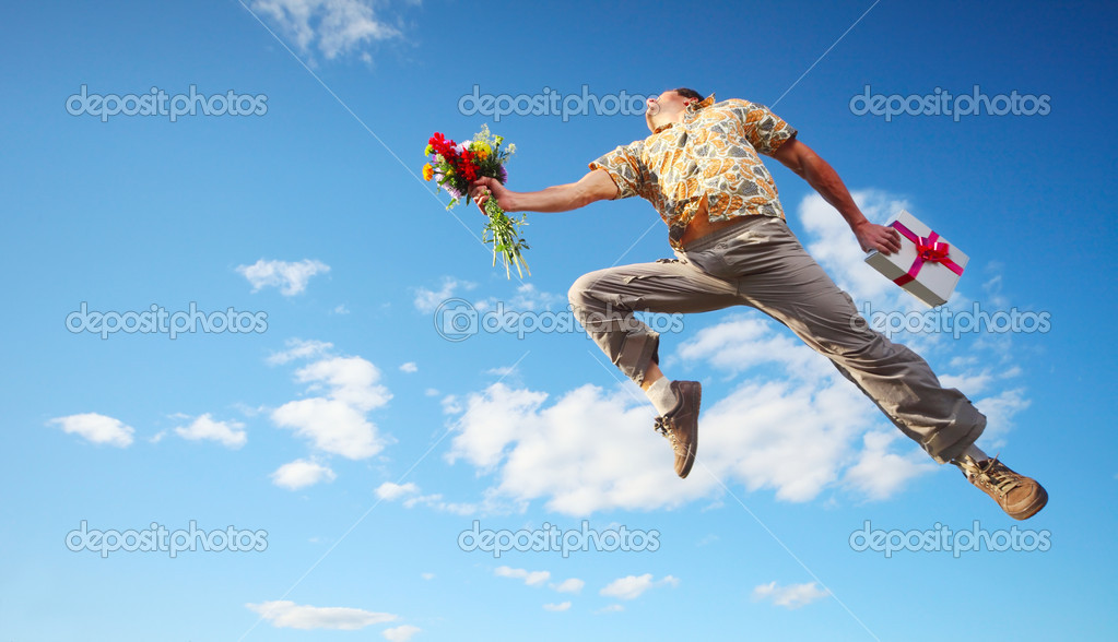 Young happy man jumping with flowers and gift box on blue sky background — Stock Photo #8149698