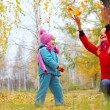 Young mother and her little daughter having fun in an autumn forest - Foto de Stock