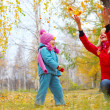 Young mother and her little daughter having fun in an autumn forest - Stock Photo