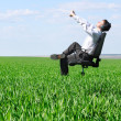 Stretching man on chair in green field — Stock Photo