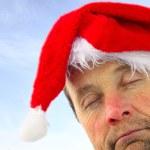 Drunk man in santa's hat over sky background — Stock Photo