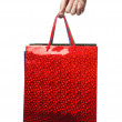 Hand holding a red bag over white — Stock Photo