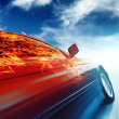 Burning car in motion over blue sky background — Stock Photo