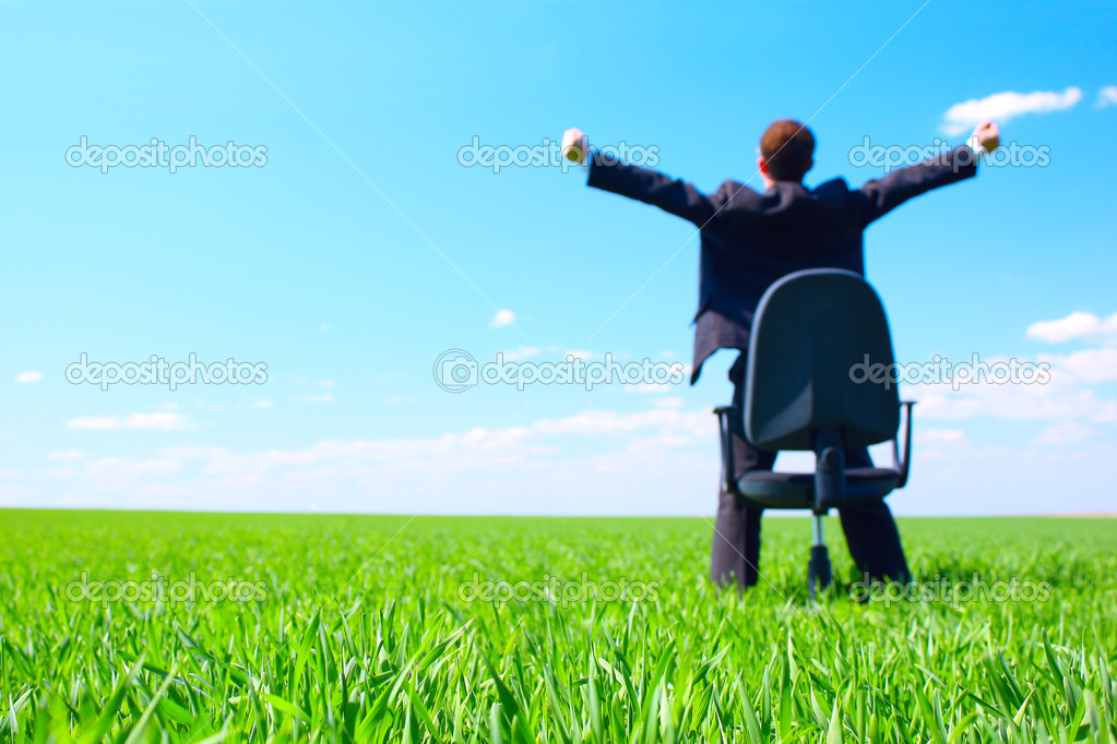 Young businessman standing on green field near chair. Focus on grass — Stock Photo #8152434