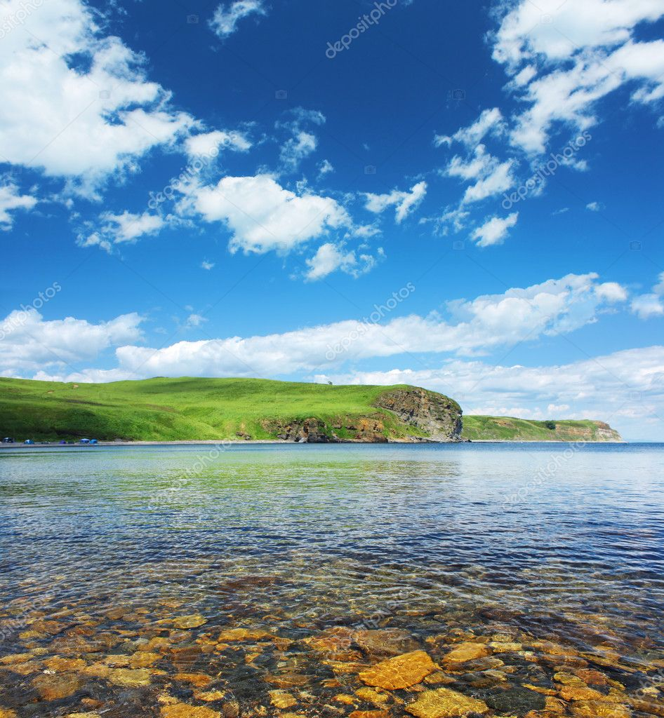 Blue sea with rocks land and blue sky with clouds  Stock Photo #8153065