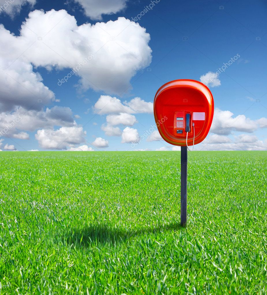 Red public phone device on green field with blue sky — Stock Photo #8153197