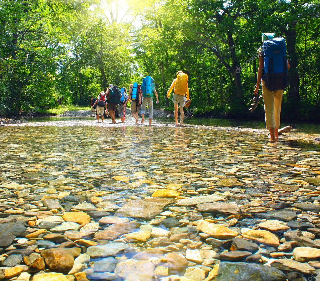Group of backpacers fording cold river — Stock Photo #8153385