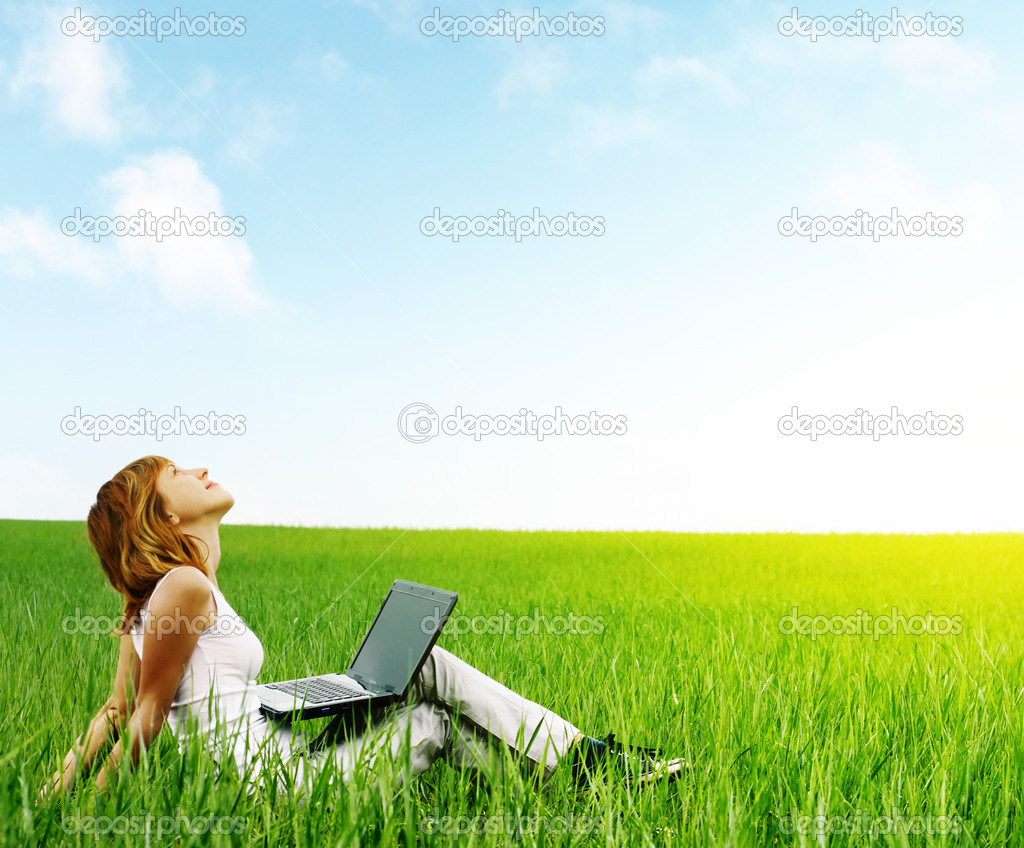 Young smiling woman with laptop sitting in meadow with green grass — Stock Photo #8155300