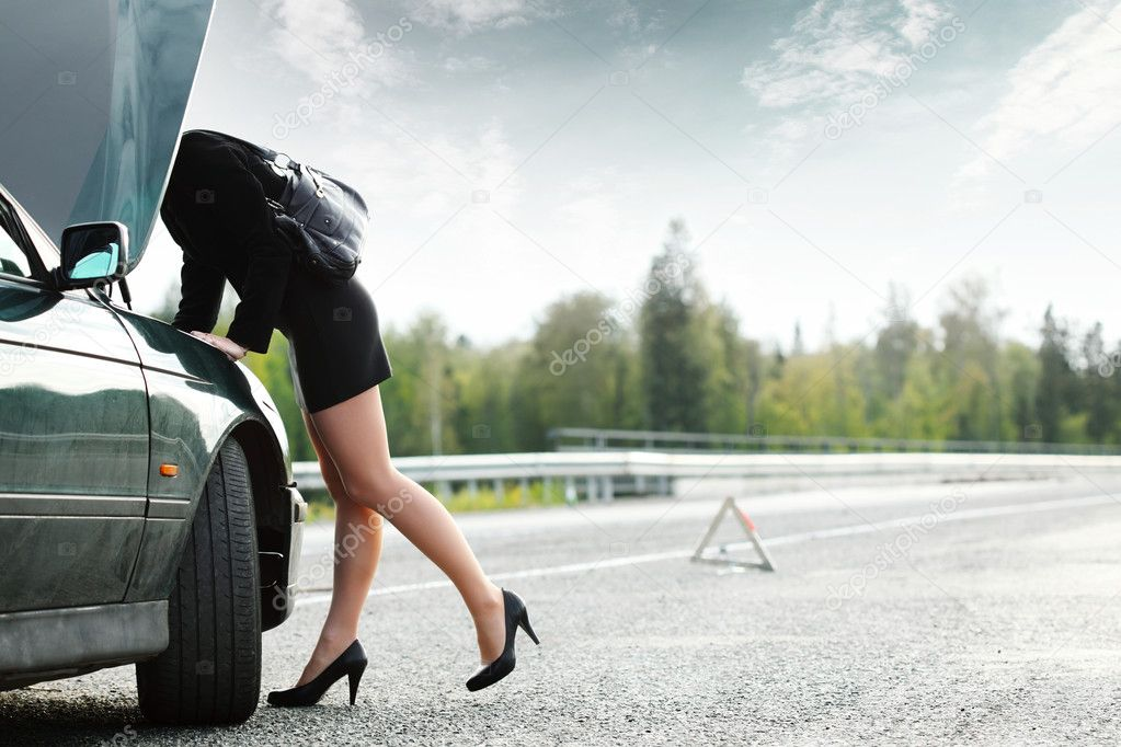 Young woman weared heels repairing her broken car — Stock Photo #8157571