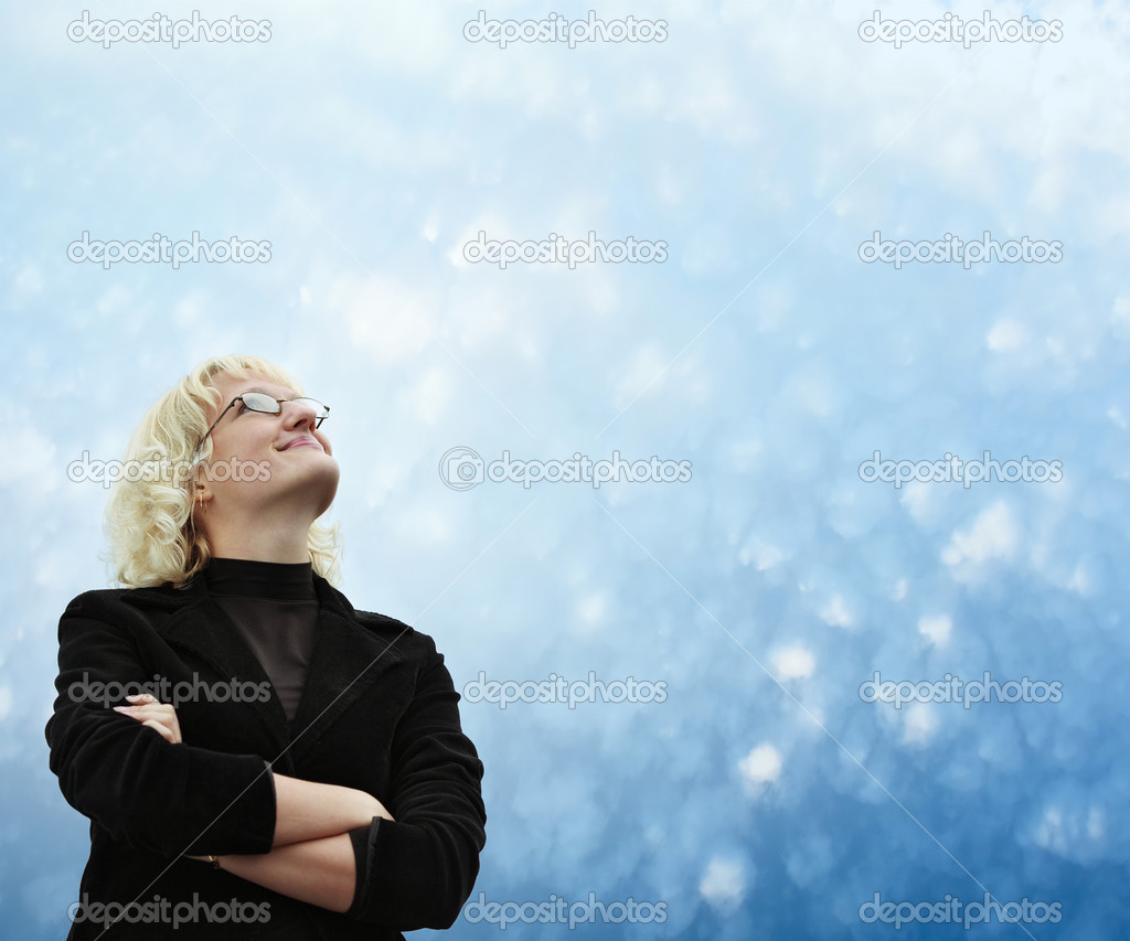 Smiling young blonde woman in glasses looking to blue sky — Stock Photo #8157961