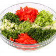 Salad vegetables and greens in a glass vase on a white backgroun — Stock Photo