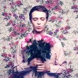 Young beautiful man with flowers - Foto Stock