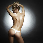 The beautiful naked sports blonde woman on a black background — Stock Photo