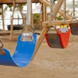 Swings in a childrens play area — Stok fotoğraf