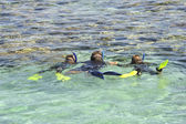 Family snorkeling in a tropical lagoon — Stock Photo