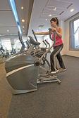 Woman on a gym machine — Stock Photo