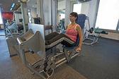 Mujer en una máquina de gimnasio — Foto de Stock