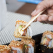 Hand using chopsticks with sushi — Stock Photo #9337763