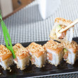 Foto Stock: Hand using chopsticks with sushi