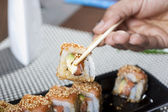 Hand using chopsticks with sushi — Photo