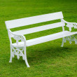 White Bench on green lawn -  