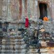 Two unidentified Buddhist monks sit and stand at Angkor Wat — Foto de Stock