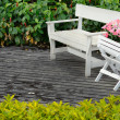 White wood chair on floor in garden — Stock Photo #9128089