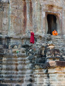 Two unidentified Buddhist monks sit and stand at Angkor Wat — Photo