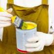 Woman in boilersuite handles brush and can with yellow paint - Stock Photo