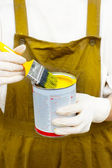 Boilersuite 的女人处理画笔,并可以用黄色颜料 — 图库照片