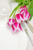 Tender pink tulips grace a table setting . Sample copy space pro — Stock Photo