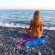 Young womsitting on stony beach — стоковое фото #10379388