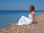 Beautiful young woman sitting on a coastline — Stock Photo