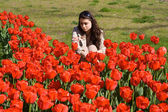 Girl in red tulips — Stock Photo