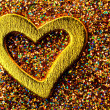 Gold shiny heart against the background of tinsel - Stock Photo