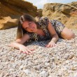 Beautiful woman on stone beach — Stock Photo