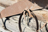 An old rusty horseshoe and hacksaw on the wall — Stock Photo