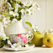 Tea cup with flower blossoms and green apples — Stock Photo