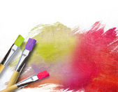 Artist brushes with a half finished painted canvas — Stock Photo