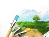 Artist brushes with a half finished painted landscape canvas — Stock Photo