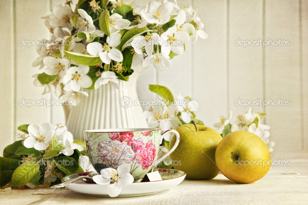 Tea cup with fresh flower blossoms and green apples — Stock Photo #10246183