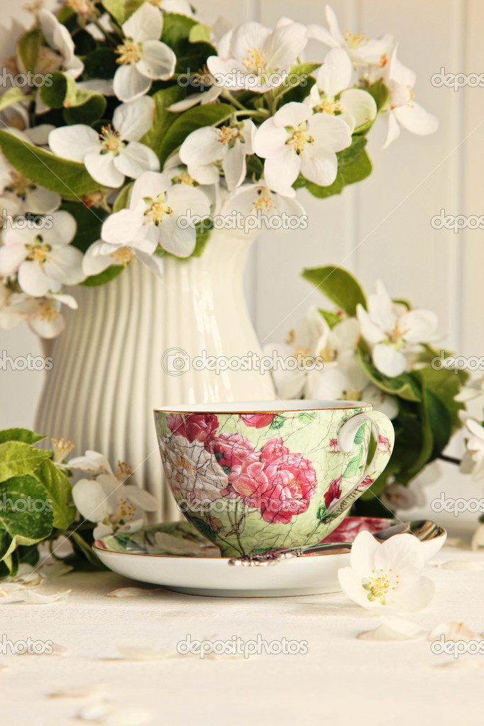 Tea cup with fresh flower blossoms on table  Stock Photo #10246189
