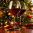 Red wine on table Christmas tree — Stock Photo