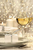 Festive table setting with silver ribbon gift — Stock Photo