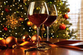 Red wine on table Christmas tree — Photo