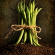 Fresh green beans tied against grunge background -  