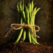 Fresh green beans tied against grunge background - Stock Photo