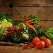 Freshly picked vegetables in basket on wooden table - Stock Photo