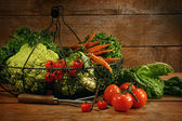 Freshly picked vegetables in basket on wooden table — Stock Photo